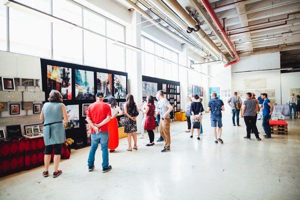 A photo of a group of people viewing artworks