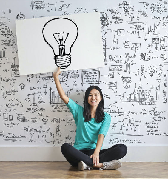 A photo of a lady pointing towards a drawn bulb