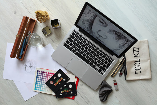 A photo of a laptop tool kit a pen case and drawing papers