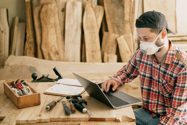 A Photo of a man using a laptop at a wood workshop