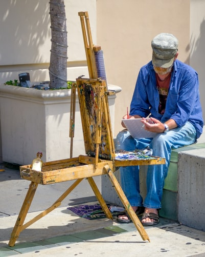 A photo of a man in blue brainstorming on a painting