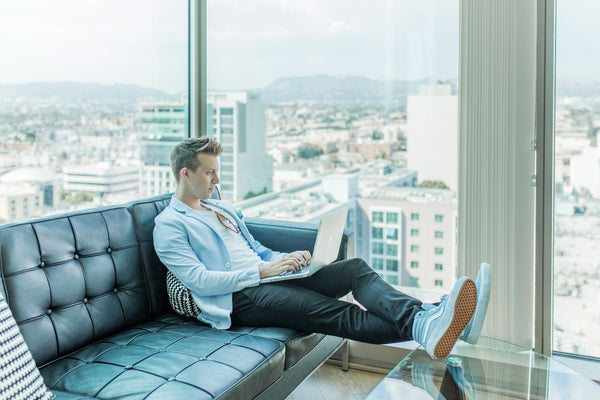 A photo of a man sitting on a sofa while using a laptop