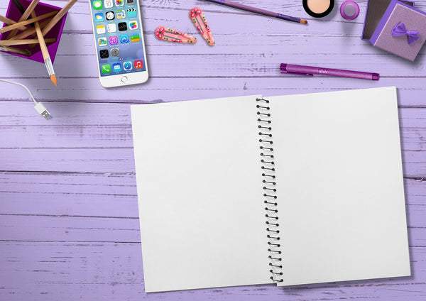 A photo of a notebook a mobile phone, clips a chord and pens
