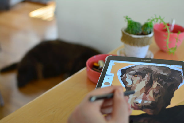 A photo of a person drawing a dog on an android tablet