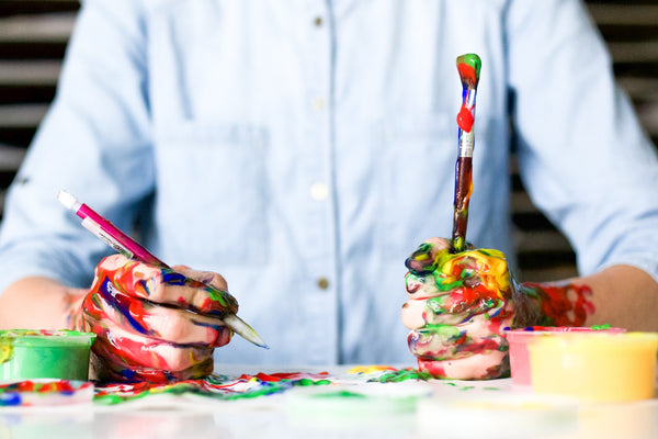 A photo of a person holding a click pen and a paint brush