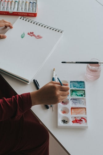A photo of a person painting with a brush on a paint pad