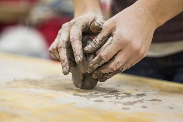A photo of a person performing a form of art called clay hand sculpting