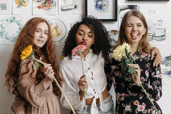 A photo of a three women holding flower