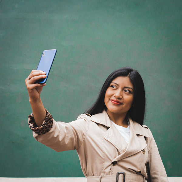 A photo of a woman in a brown coat taking a selfie with a phone