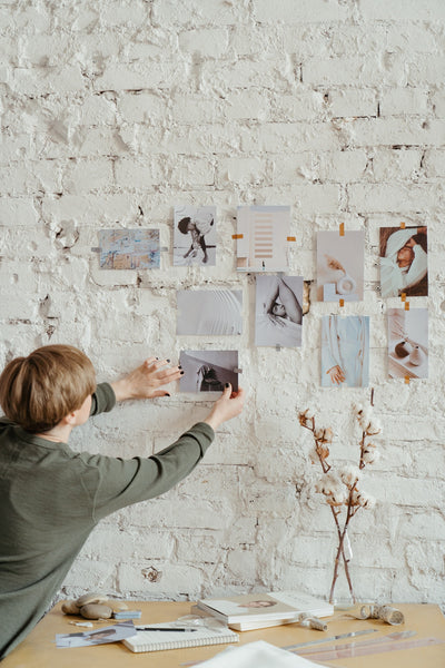 A photo of a woman in gray long sleeve shirt placing photos on a white brick wall