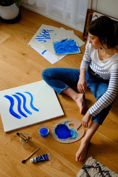 A photo of a woman on a wooden floor painting on various white sheets of paper