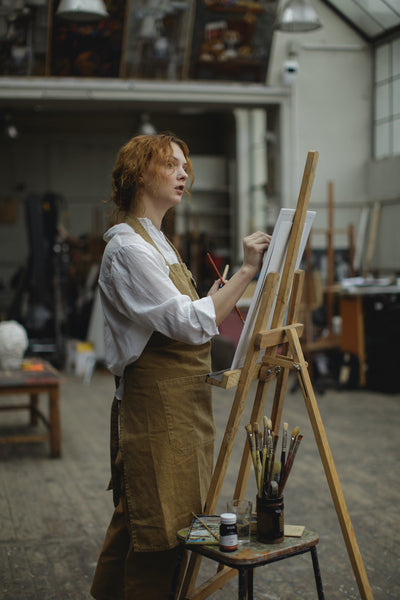 A photo of a young woman in brown apron sketching on white cardboard