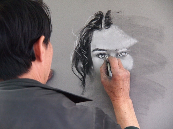 A photo of an artist drawing with pencil
