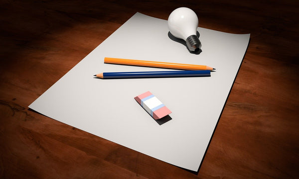 A photo of an empty paper two pencils an eraser and a lightbulb on a wooden table