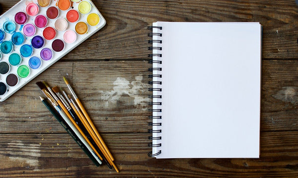 A photo of art water colors paintbrushes and a jotter on a wooden platform