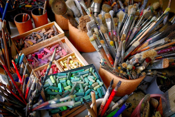 A photo of brushes multi colored chalks and pencils