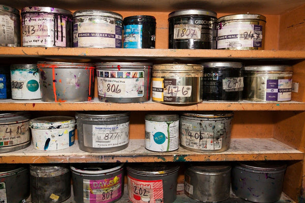 A photo of color cans of paint clamping colors