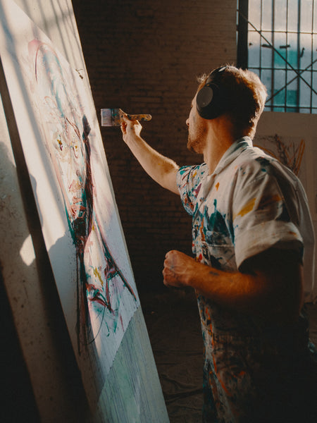 A photo of man in an overall painting on a white board