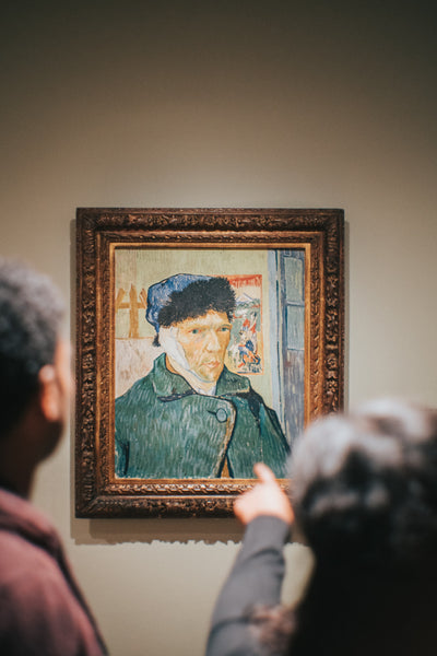 A photo of two persons standing near a vincent van gogh self portrait