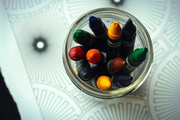 A photo of various colors of crayons in a jar