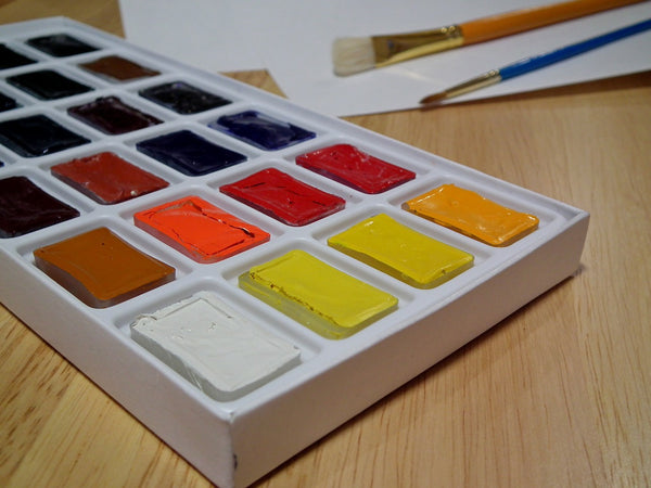 A photo of water colors paint with paint brushes and a white paper