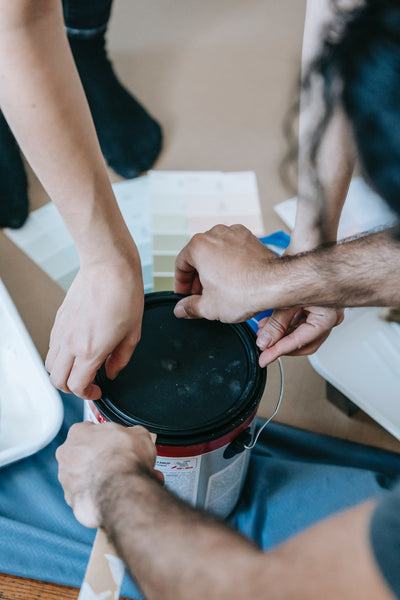 A photo two people opening a can of paint