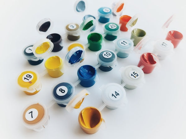 A photo various paint by numbers pots on a white platform