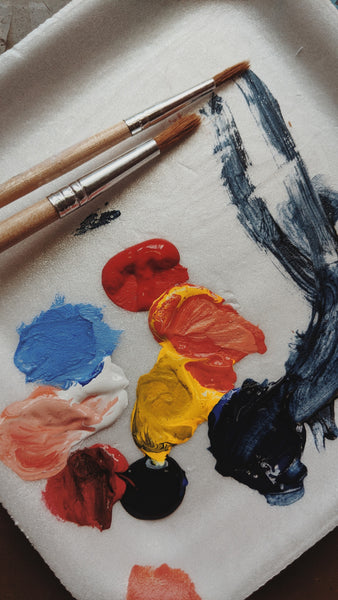 A red yellow blue and black paint with paint brushes