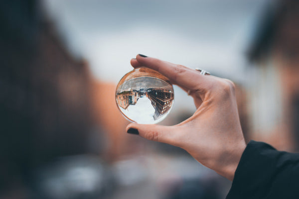 A selective focus photography of a woman holding clear glass