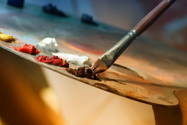 A shallow focused photograph of a paintbrush being used