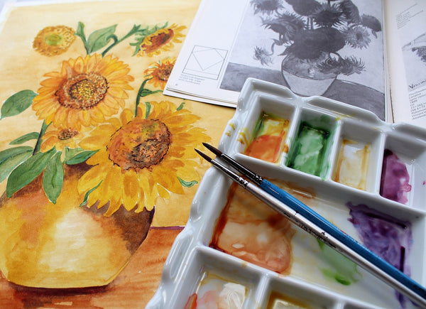 A water colored yellow flowered painting with paint brushes and a sketch book