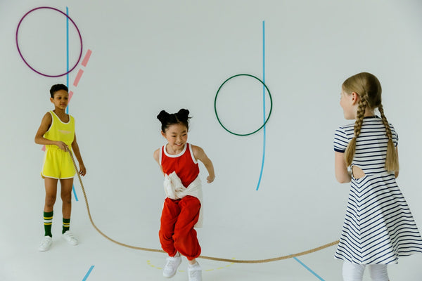 A white background photo of 3 kids playing skip the rope and hoops