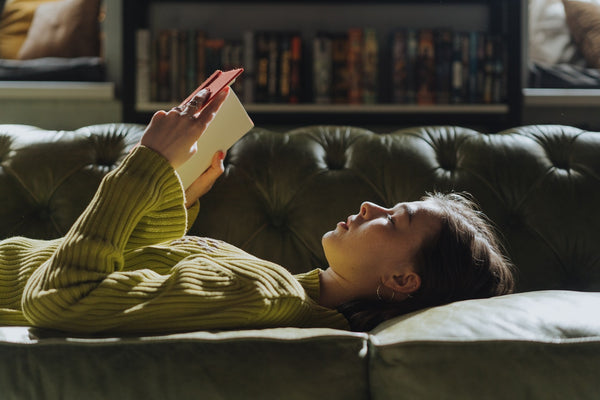 A woman in yellow long sleeve shirt lying on a couch
