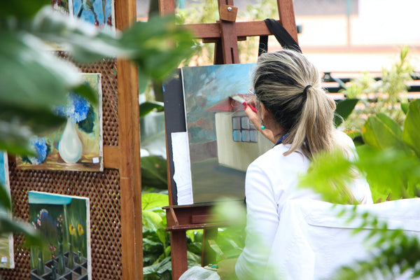 A woman painting a canvas outside