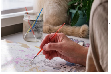 The older Woman's hand holds a brush she painting