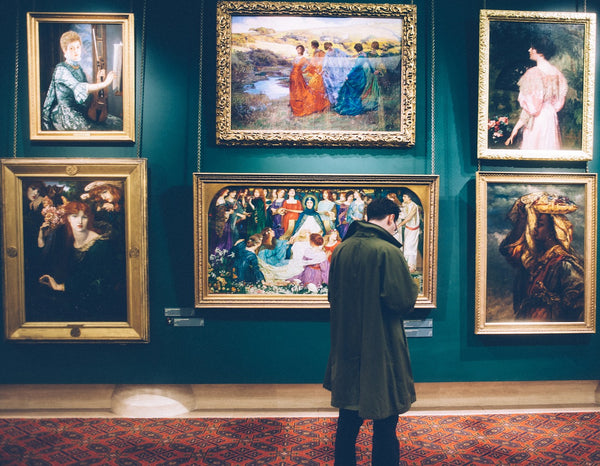 A man standing in front of numerous paintings