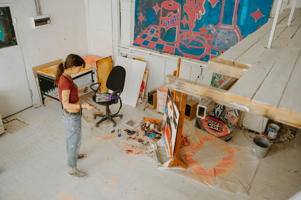 A female artist standing up and looking at her painting