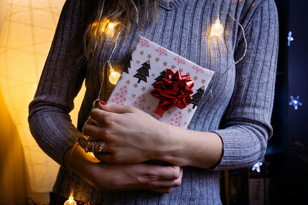 A lady holding a gift wrap in white gift paper