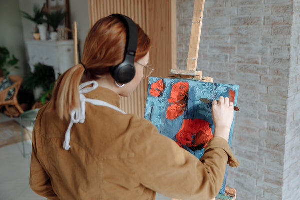 A lady painting with her headsets on