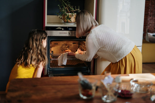 A lady teaching her daughter how to bake