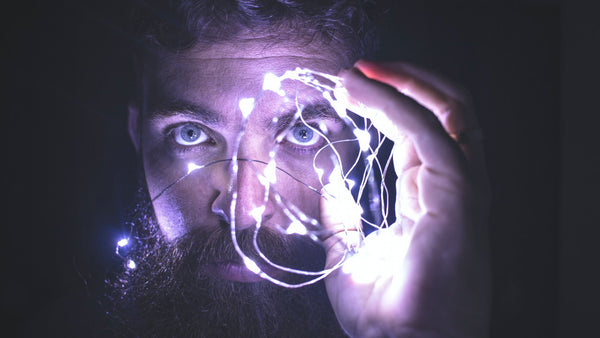 A man holding some string lights