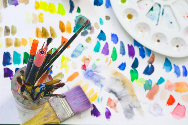 paint and paint brushes with a palette all on a white canvas sheet