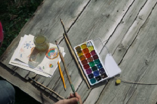 paintbrushes, a jar, a paint set and water color paint sheets