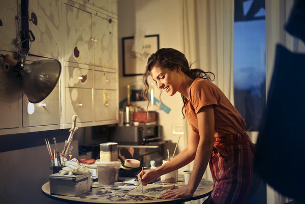 Photo of woman painting while smiling and standing by the table