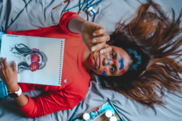 Woman with colorful paints on face lying on bed with sketchbook
