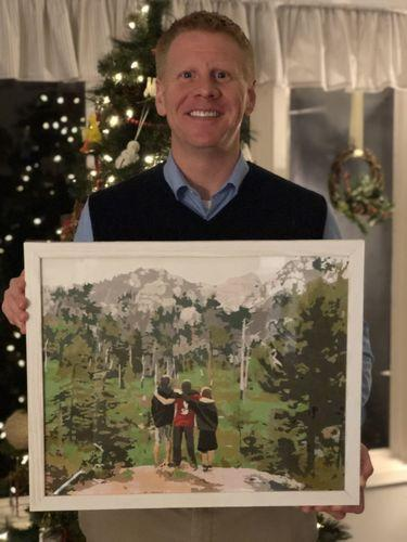 A men is holding a self painted picture that he painted with a paint by number kit. Christmas tree in background.