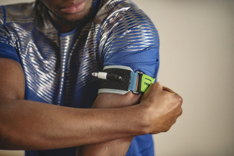 Man putting on and adjusting his B Strong Blood Flow Restriction Training Bands on his bicep