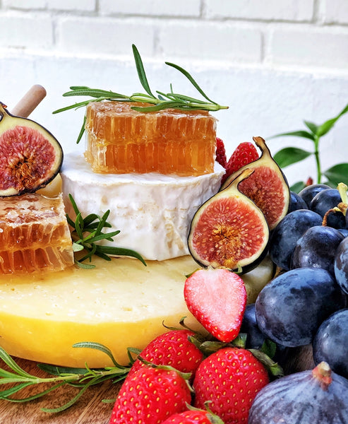 Splatter's two-tiered artisan cheese wheel cake topped with raw honeycomb, surrounded by fresh grapes, strawberries, and figs
