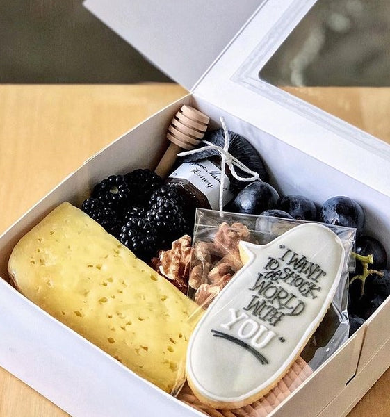 White gift box filled with artisanal cheese, designer cookie, and other accompaniments in black and grey colour scheme.