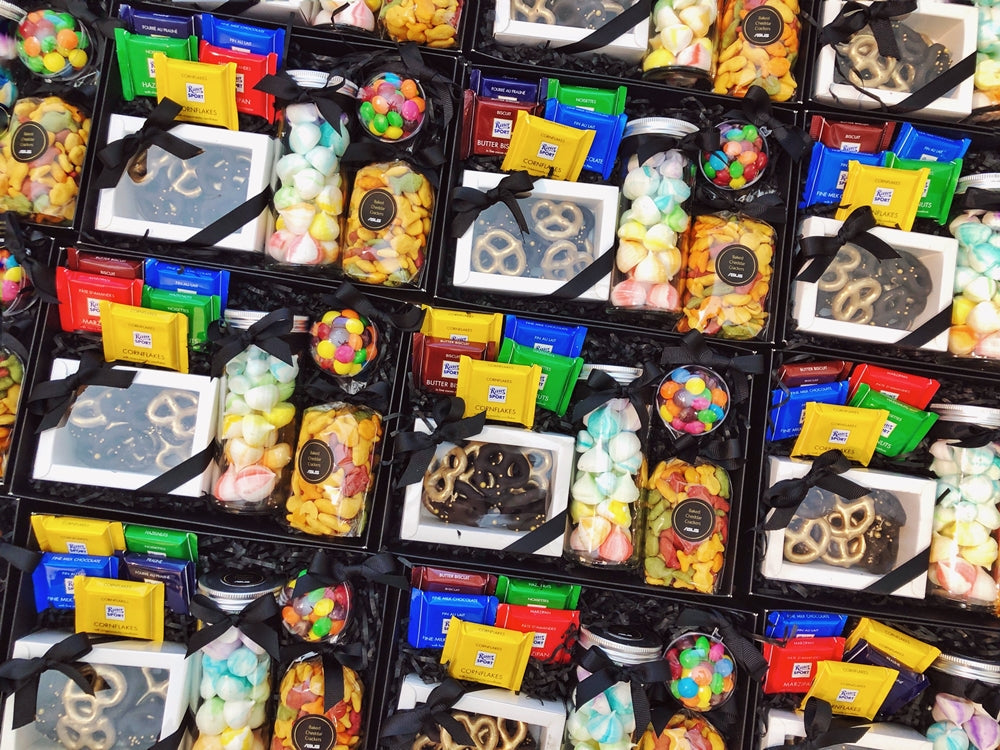 Corporate gift of black boxes filled with colourful chocolates and snacks